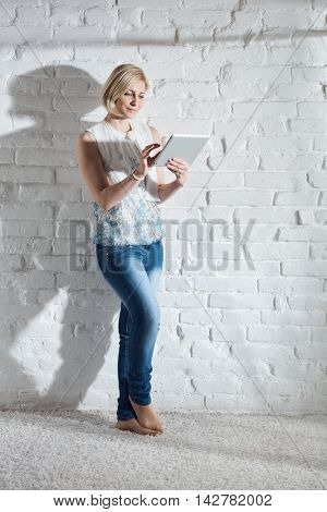 Casual young woman standing by white brick wall, using tablet computer. Full size.