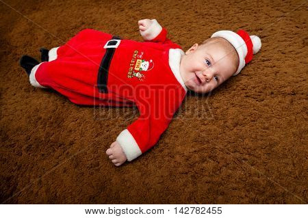 A growing baby boy celebrates his first Christmas in a sleeper and Santa hat that are too small for him. He is laying on the carpet and smiling for the camera.