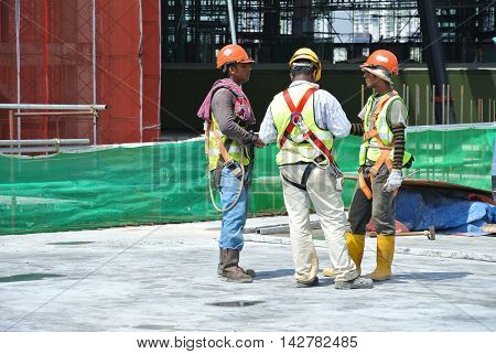 KEDAH, MALAYSIA -MAY 14, 2016: Construction workers discuss among themselves at the construction site.
