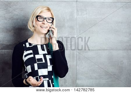 Old-fashioned woman standing by wall, talking on mobilephone.