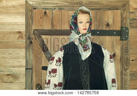 A dummy of the woman in a beautiful national historic outfit stands near the door of a wooden rural house.