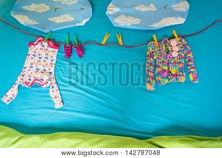 Colorful and small baby clothes hanging under the sun