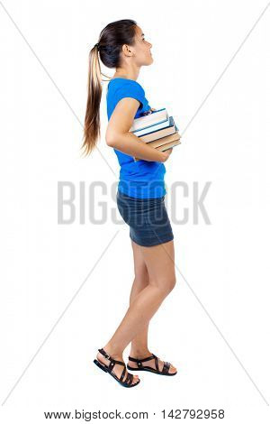 Girl comes with  stack of books. side view. Rear view people collection.  backside view of person.  Isolated over white background. girl in a short skirt and a blue T-shirt goes to the side with a