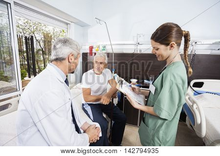 Senior Patient Looking At Doctor While Nurse Holding Reports