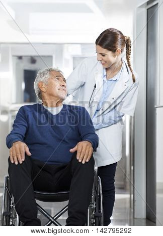 Doctor Looking At Senior Patient On Wheel Chair