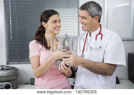 Vet And Woman Holding Ill Rabbit In Clinic