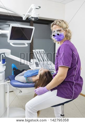 Dentist Wearing Loupes While Examining Patient In Clinic