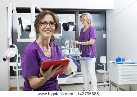 Smiling Assistant Holding Digital Tablet While Colleague Working