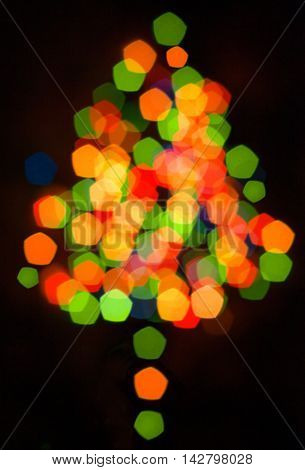 Defocused multicolored christmas tree silhouette with blurred lights