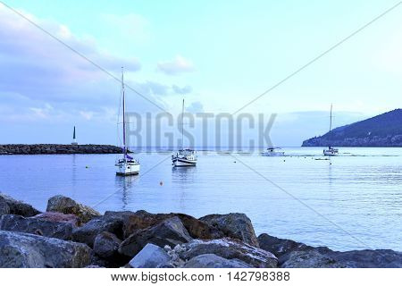 Evening scene after sunset, blue hour at a bay or harbor with anchored sailing ships and beacon.