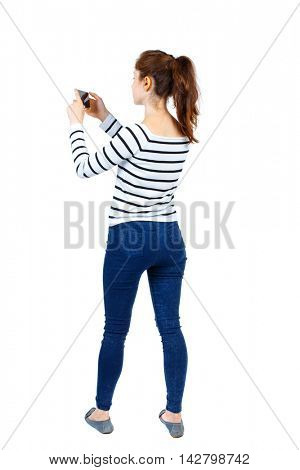 back view of standing young beautiful  woman  using a mobile phone. girl  watching. Rear view people collection.  backside view of person.  Isolated over white background. Girl in striped sweater