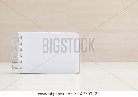 Closeup surface blank space at page of note book on blurred brown wood desk and wood wall textured background with copy space under window light