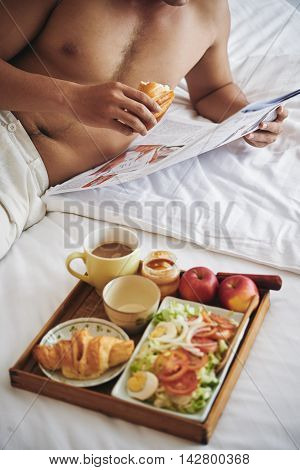 Young man reading news when having breakfast in bed
