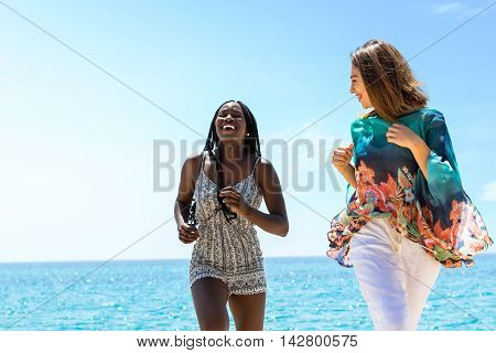 Close up action portrait of african woman and caucasian girlfriend laughing and running together on beach.