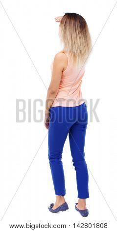 back view of standing young beautiful  woman.  girl  watching. Rear view people collection.  backside view of person.  Blonde in blue pants gazes somewhere ahead.