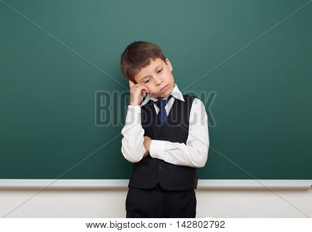 school student boy posing and think at the clean blackboard, grimacing and emotions, dressed in a black suit, education concept, studio photo