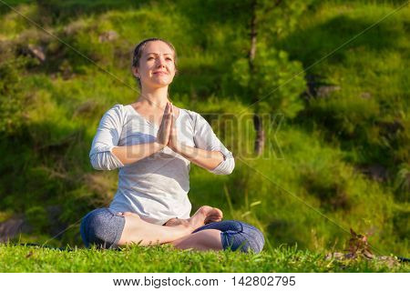 Meditation and relaxation yoga outdoors - young woman meditating and relaxing in Padmasana Lotus Pose) with namaste mudra on green grass in forest