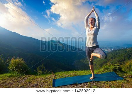 Yoga practice outdoors - woman practices balance yoga asana Vrikshasana tree pose in Himalayas mountains outdoors in the morning. Himachal Pradesh, India. Panorama