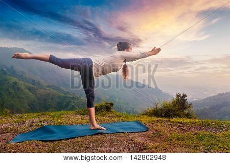Yoga outdoors - sporty fit woman doing Ashtanga Vinyasa Yoga asana Virabhadrasana 3 Warrior pose posture in mountains