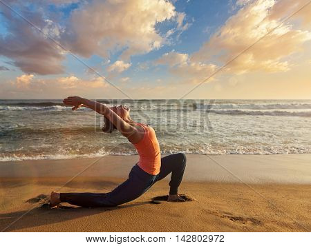Yoga outdoors - sporty fit woman practices yoga Anjaneyasana - low crescent lunge pose outdoors at beach on sunset