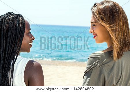 Close up face shot of two teen friends looking at each other outdoors.African girl looking at caucasian friend.