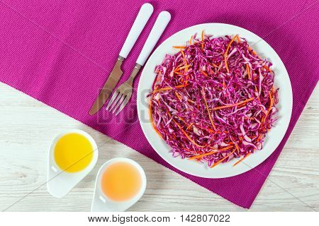 Salad coleslaw - red cabbage with carrots on white dish with fork and knife on table mat olive oil and apple vinegar in garvy boats Vegetarian healthy food authentic classic recipe view from above