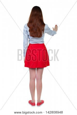back view of woman. Young woman presses down on something. Isolated over white background. Rear view people collection. backside view of person. Long-haired brunette in red skirt presses his hand on