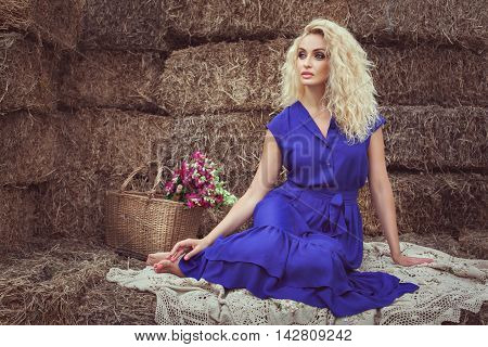 Beautiful blonde woman in the hayloft in the village she is dreaming and waiting.