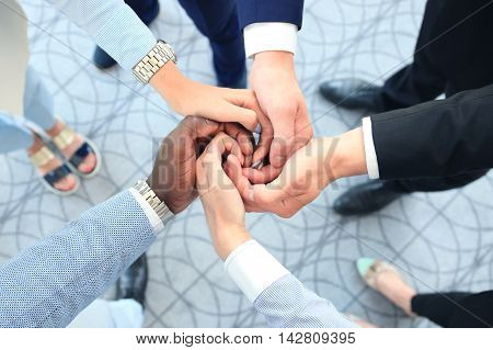 Multiethnic group of young people putting their hands on top of each other. Close up image of young business people making a stack of hands.