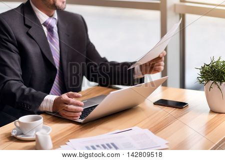 Diligent worker. Pleasant senor busy businessman sitting at the table and holding papers while working