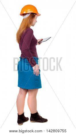 Backview of business woman in construction helmet stands and enjoys tablet or using a mobile phone. Standing young girl. Rear view people collection.  backside view of person.  Isolated over white
