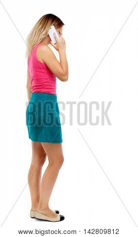 back view of a woman talking on the phone.  backside view of person.  Rear view people collection. Isolated over white background. Blonde in a red sweater and green skirt is a serious conversation on