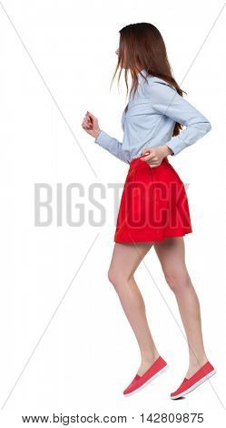 side view of running  woman. beautiful girl in motion. backside view of person.  Rear view people collection. Isolated over white background. Long-haired brunette in red skirt runs in the side.