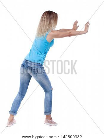 back view of woman pushes wall.  Isolated over white background. Rear view people collection. backside view of person. The blonde in a blue shirt and jeans, put her hands on the wall.