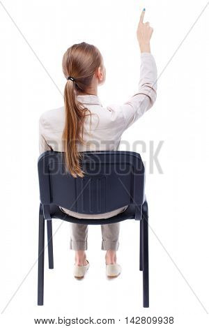 back view of young beautiful  woman sitting on chair and pointing.  girl  watching. Rear view people collection. Skinny girl in white denim suit sitting on an office chair and shows up finger.