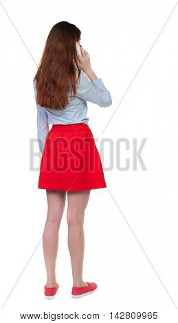 back view of a woman talking on the phone.  backside view of person.  Rear view people collection. Isolated over white background. Long-haired brunette in red skirt and white talking on a smartphone.
