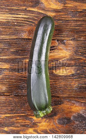 a fresh zucchini on a natural brown wooden background. Zucchini is vertical.