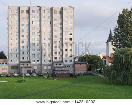 JELENIA GORA POLAND - AUGUST 14 2016: industrialized apartment block with church in the background in Jelenia Gora Poland