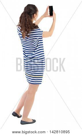 back view of standing young beautiful  woman  using a mobile phone. girl  watching. Rear view people collection.  backside view of person.  Isolated over white background. Swarthy girl in a checkered