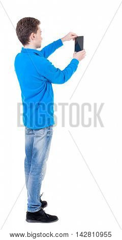 back view of standing business man photographing a phone or tablet. Rear view people collection.  backside view of person.  Isolated over white background. Curly boy in the blue jacket photographs