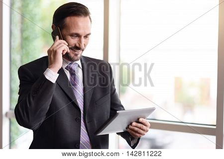 Business affairs. Cheerful smiling senior businessman using tablet and talking on cell phone while standing near window