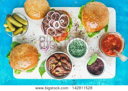 Homemade beef burgers with onion rings, pickles, fresh vegetables, spices, sun-dried tomatoes and tomato sauce on serving wooden board over blue painted background. Top view, horizontal composition