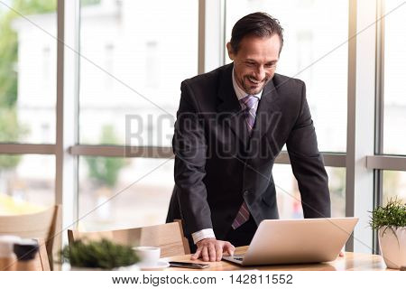 Full of gladness. Positive content senior man standing near table and using laptop while feeling cheerful
