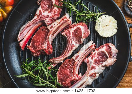Raw uncooked lamb meat chops with rosemary and garlic in black iron grilling pan, top view, horizontal composition