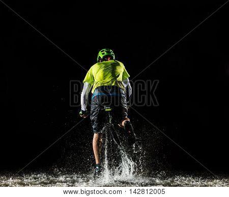 Mountain biker at night riding through forest stream and splashing water around. Backside-view