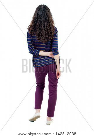 back view of standing young beautiful  woman.  girl  watching. Rear view people collection.  backside view of person. Long-haired curly girl in blue jacket standing with his hands crossed behind his