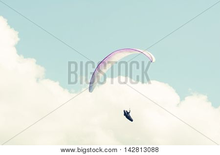 Paraglider Flying Into The White Clouds