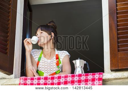 Portrait of relaxing young woman with cup of freshly brewed coffee in Italian moka pot and sitting near open window with traditional European wood brown shutters.