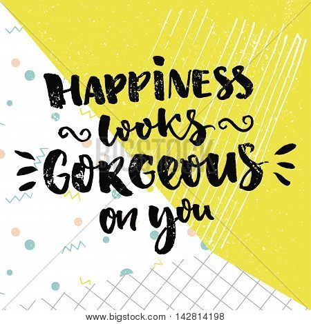 Happiness looks gorgeous on you. Inspirational quote and kind wish. Vector calligraphy design on colorful background with green, dots and squared paper.