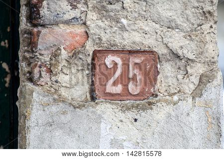 house number Twenty-five sign at old wall